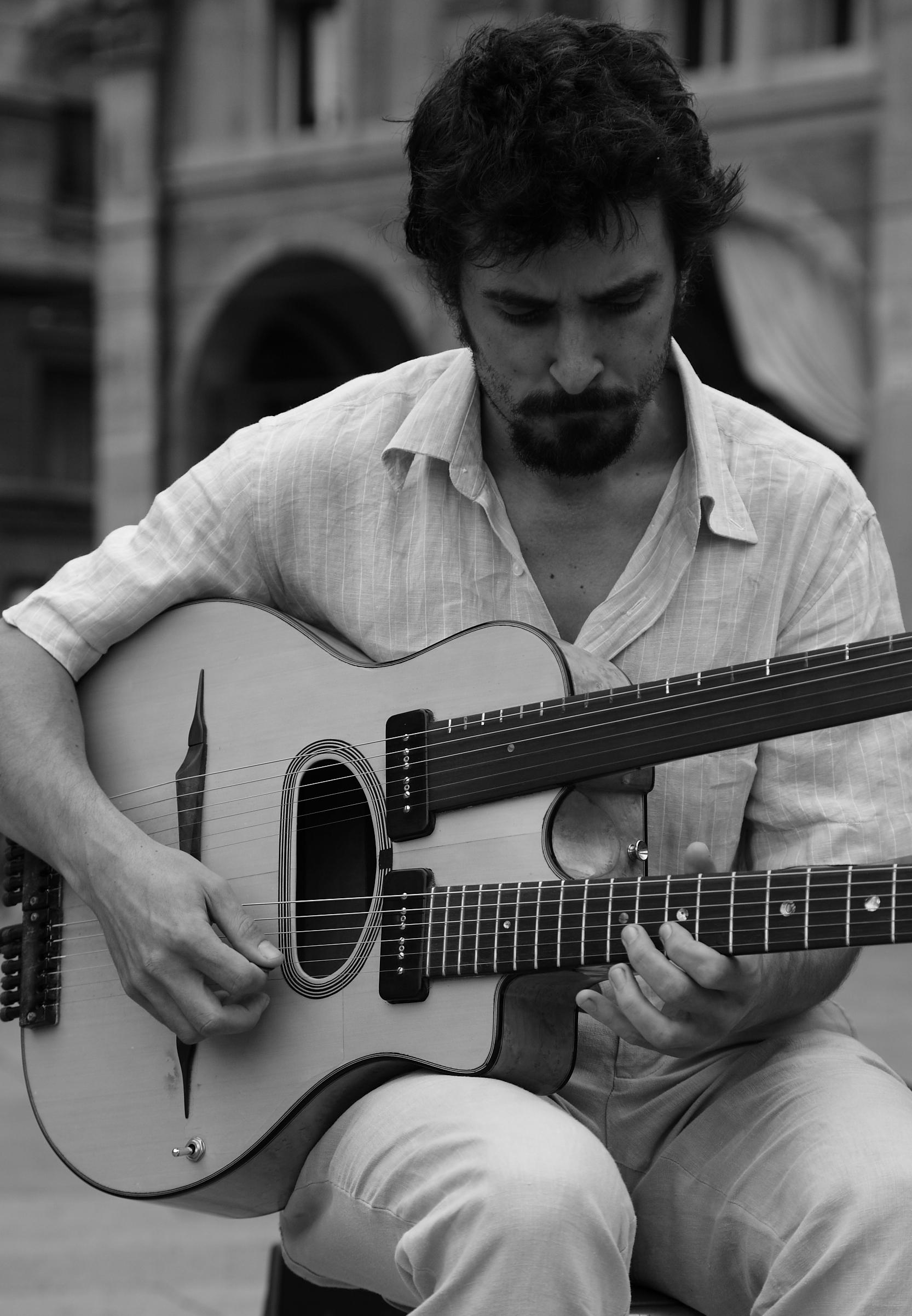 Tolga During Double neck guitar. Piazza Maggiore, Bologna
